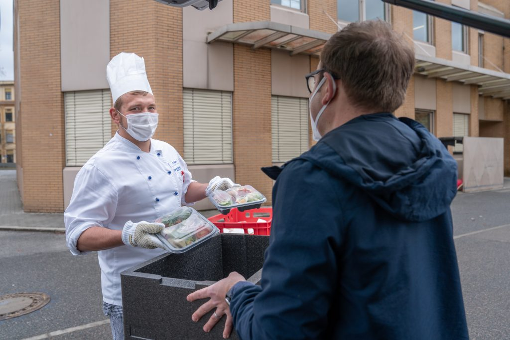Patrick Sauer (links), Küchenmeister der Verpflegungsdienste Freudenberg, überreicht Essensspende an Caritas-Mitarbeiter.